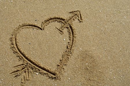 Hand drawn heart on the sand detail photo