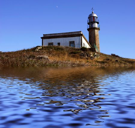 old spanish lighthouse and the reflection on the water photo