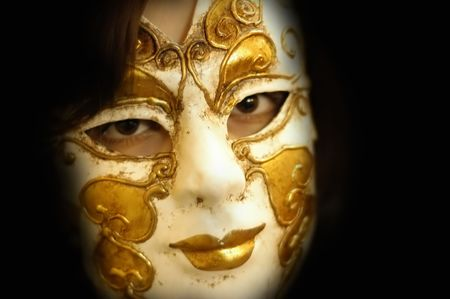 inscrutable: woman with a venice mask in a dark place Stock Photo