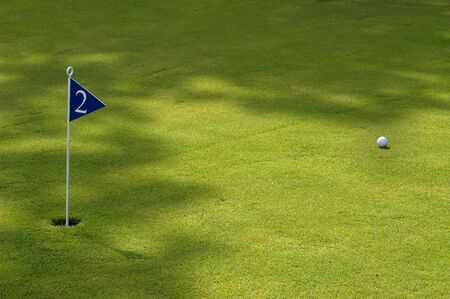 ball and flag in a green golf field photo