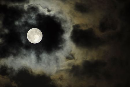 big moon over the clouds in a dark night photo