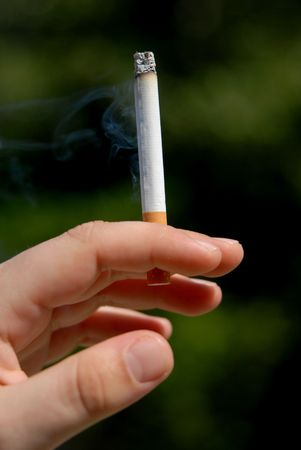 unhealthiness: man hand with a cigarette among green vegetation Stock Photo