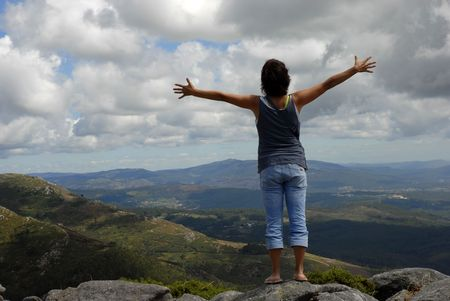 woman with arms wide open in the mountain photo