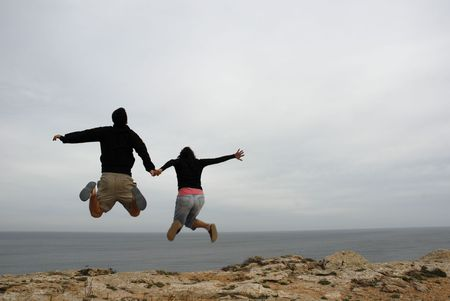 couple jump together holding hands at the coast photo