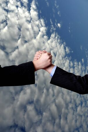men shake hands with white clouds and blue sky photo