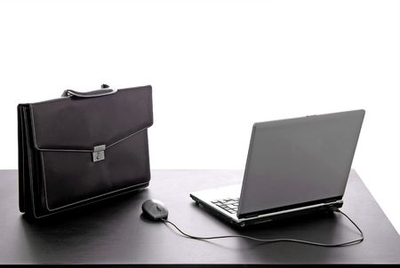 laptop and a suitcase on a office desk