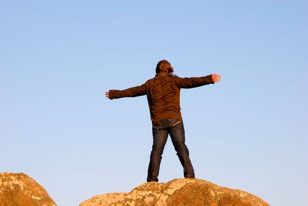arms wide open: young man with arms wide open on the rocks