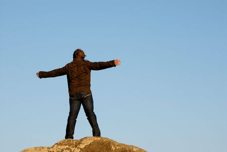 young man with arms wide open and the sky as background Stock Photo - 1834800
