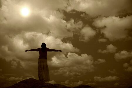 arms wide open: woman with arms wide open at the coast in sepia