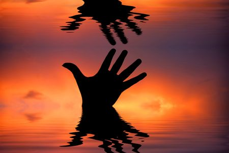 human hand with water reflection at sunset photo