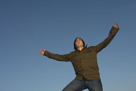 arms wide open: young man with arms wide open and the sky