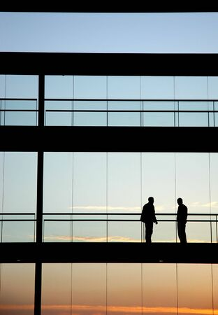 two workers inside the building silhouette at sunset 스톡 콘텐츠