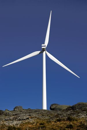 white wind turbine in the top of the mountain photo