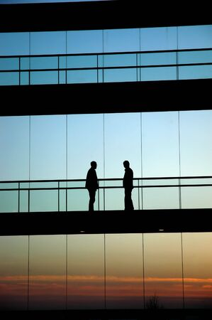 business life line: two workers inside the building silhouette at sunset Stock Photo