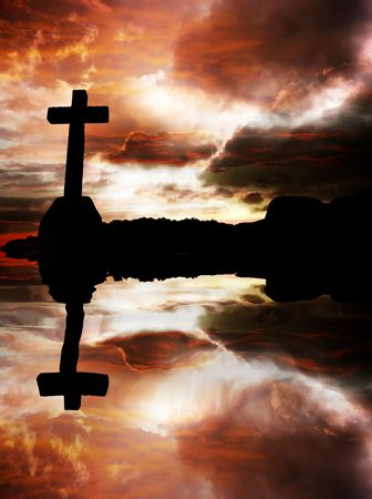 almighty: cross silhouette at sunset with water reflection                                Stock Photo