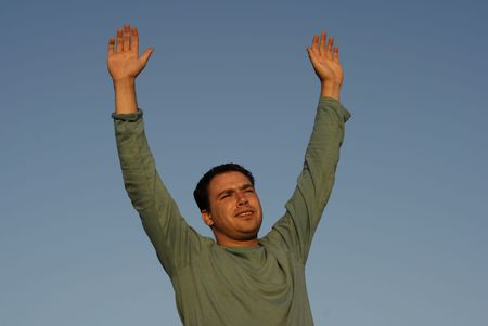 arms wide open: young man with arms wide open at sunset light Stock Photo