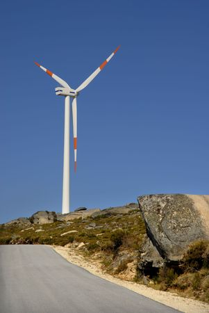 conservational: photo of a road with wind turbine on the mountain