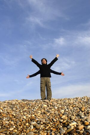 triumphant: two men with arms wide open at the beach Stock Photo