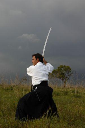 samoerai: jonge aikido man met een zwaard buitenshuis