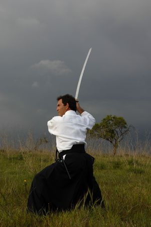 aikido: young aikido man with a sword outdoors