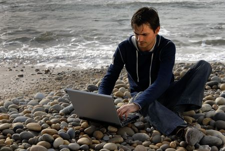 young casual man with laptop at the beach Stock Photo - 2888864