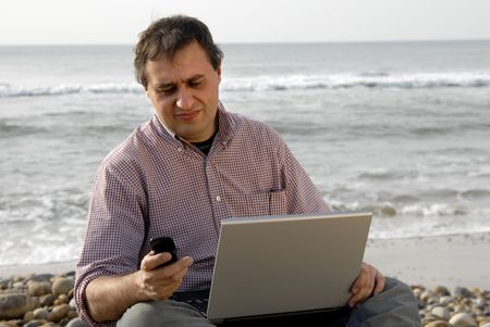 important phone call: young casual man with laptop at the beach Stock Photo