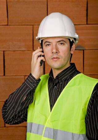 engineer with white hat with a brick wall as background photo