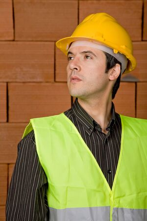 engineer with yellow hat with a brick wall as background photo