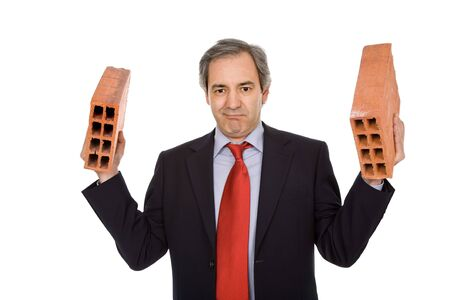 mature business man with two bricks, on white photo