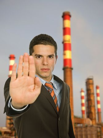 businessman with open hand making stop to pollution photo