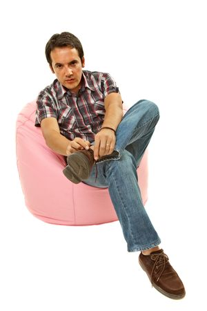 young casual man seated in a small sofa Stock Photo - 6853910