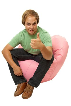 young casual man seated in a small sofa going thumb up Stock Photo - 7336288