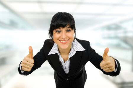 happy employee: young business woman portrait going thumbs up