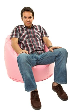 young casual man seated in a small sofa  photo