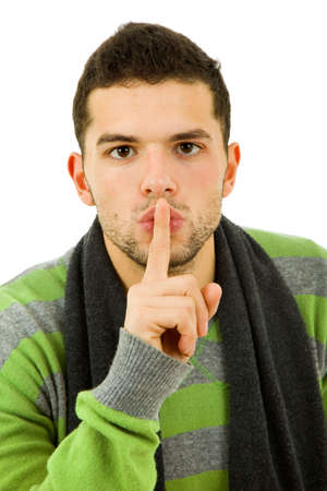 noiseless: young man showing silence gesture with his finger in the mouth Stock Photo