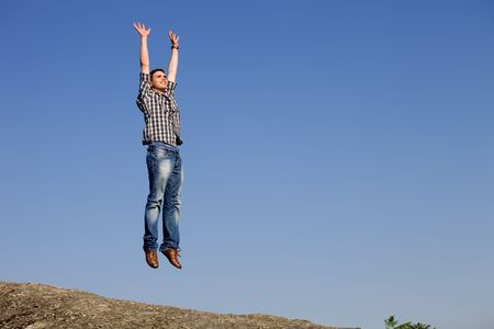 young happy man, with a big jump, on top of a rock photo