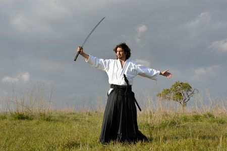 young aikido man with a sword outdoors  photo