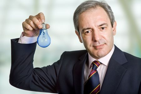 mature business man holding a blue lamp Stock Photo - 8247602