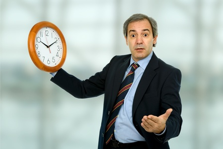 mature handsome business man holding a clock photo