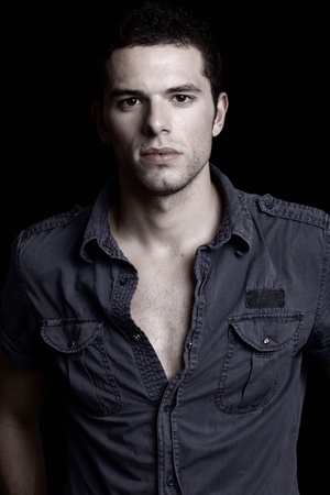 muscle shirt: young man portrait, on a black background