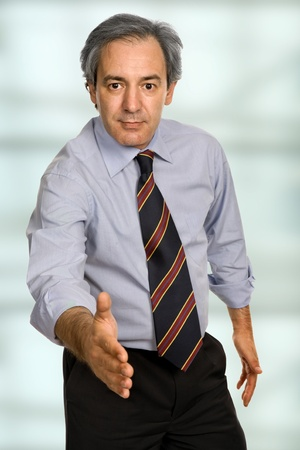 mature man in suit offering to shake the hand photo