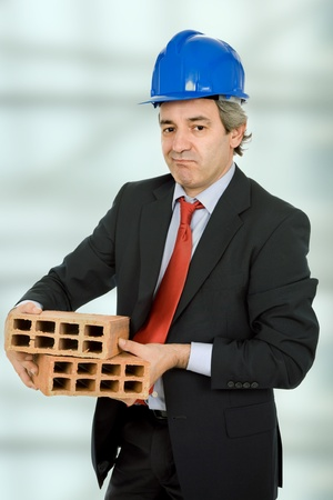 unhappy mature business man with two bricks photo