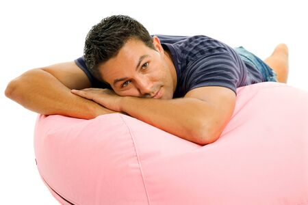 sexy gay: young casual man seated in a small sofa Stock Photo