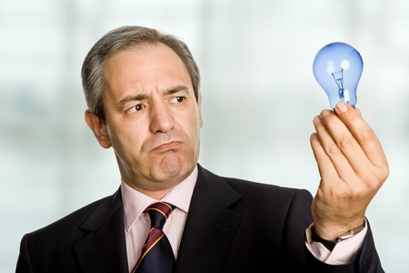 mature business man with a lamp at the office photo