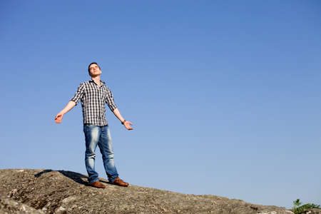 young casual man with the sky as background photo
