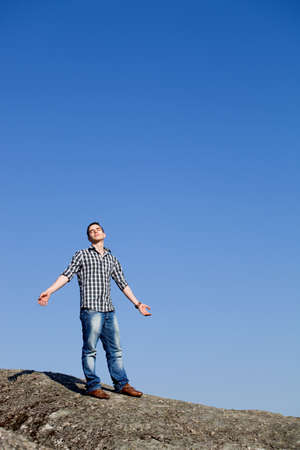 muscle formation: young casual man with the sky as background