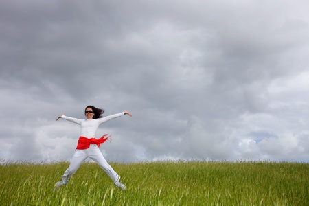 beautiful young woman jumping on field with a red scarf photo