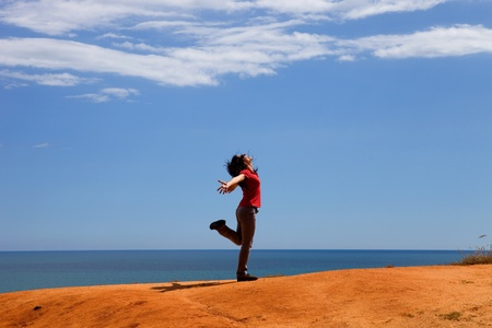 young happy woman at the coast with open arms photo