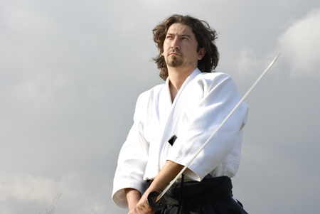 young aikido man with a sword, outdoors photo