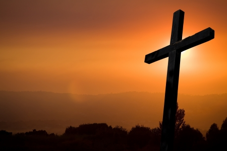 black jesus: cross silhouette with the sunset as background